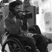 """Behind the scenes"" - Camera man who uses a wheelchair is in deep concentration as he films an interview."